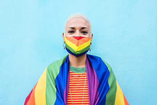 Young lesbian woman wearing rainbow mask and flag - Lgbt and gay pride concept