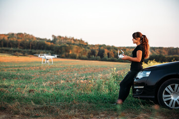 Wall Mural - A woman standing near the car launches a drone. drone flight in yellow field
