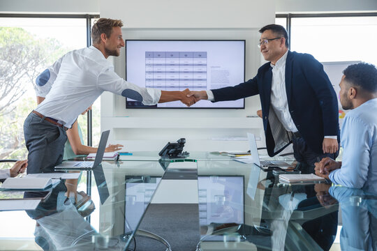 Senior businessman shaking hands with young businessman in meeting room in modern office