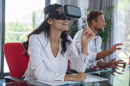 Professional businesswoman using virtual reality headset while sitting in modern office