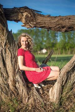 sinnliche junge Frau sitzt am Baum