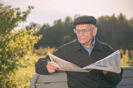 Elderly man wearing cap and glasses reading newspaper sitting on wooden bench in city public park