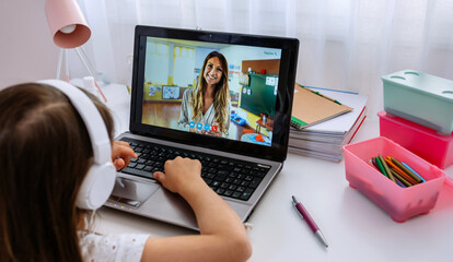 Laptop of a girl with teacher teaching class via videoconference