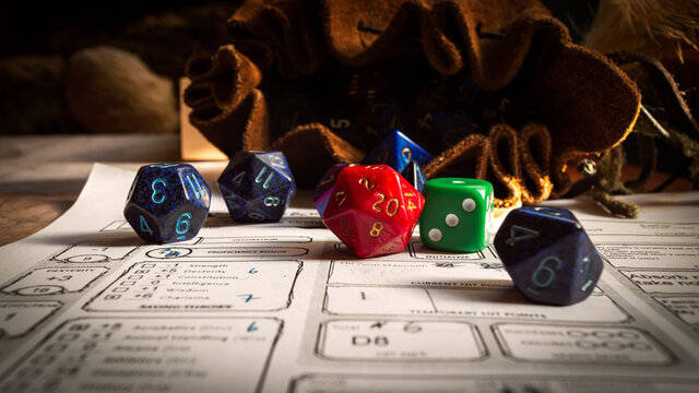 Close up of spilling out dice of different kinds from a dice bag on a character sheet.