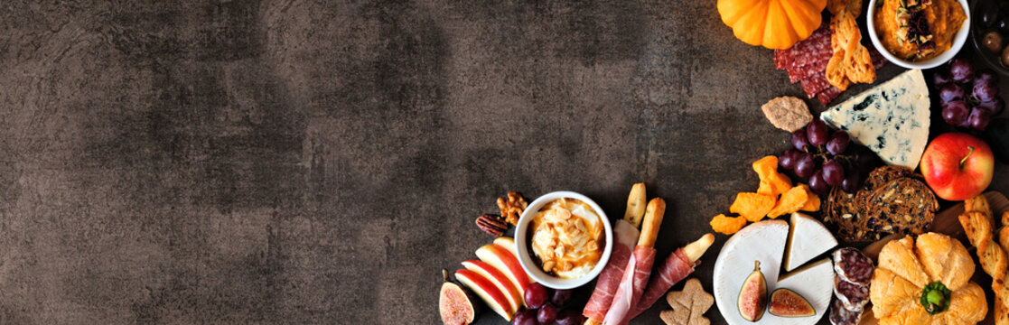 Autumn charcuterie corner border against a dark stone banner background. Selection of cheese and meat appetizers. Copy space.