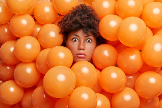 Surprised birthday girl poses over inflated orange party balloons stares bugged eyes expresses great wonder or surprise. Young Afro American woman enjoys anniversary event has shocked expression