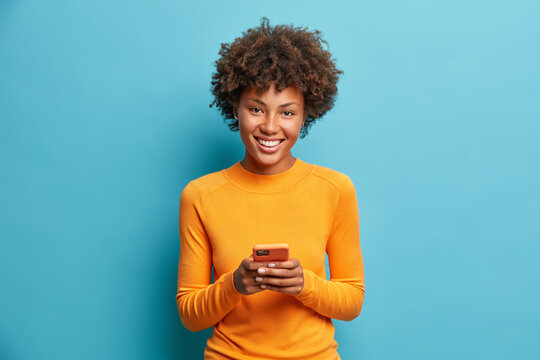 Photo of cheerful dark skinned young woman holds modern device in hands browses her favorite web page surfs social media sends sms smiles positively dressed casually isolated on blue background