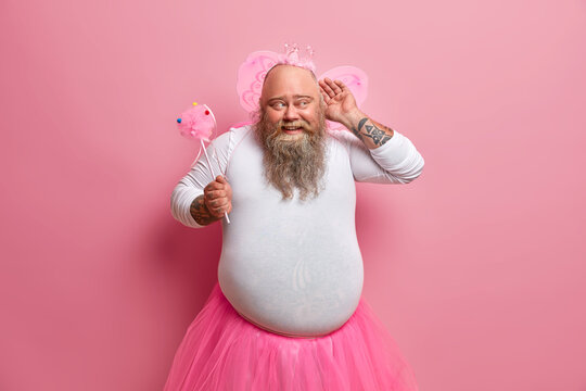 Funny overweight bearded man dressed in fairy costume to entertain guests of party keeps hand near ear and tries to overhear something holds magic wand has big belly poses against pink background