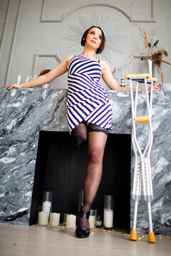 female amputee model stands in front of the fireplace next to crutches