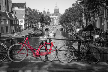 A picture of a red bike on the bridge over the channel in Amsterdam. The background is black and white.