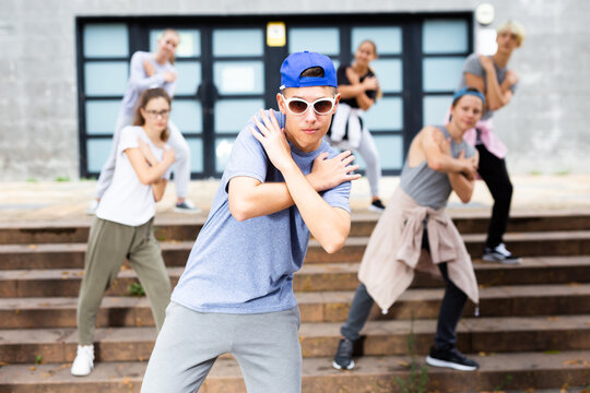 Positive teen boy dancing modern street dance outdoors with teenagers in background.