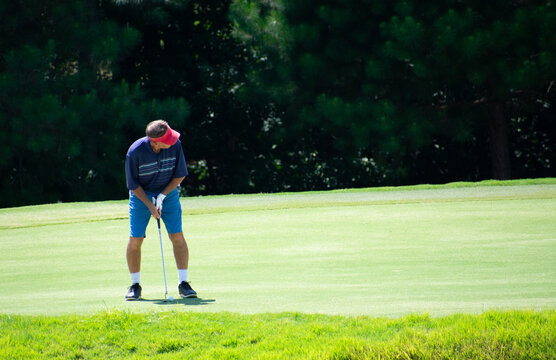 A man golfer putting a golf ball on a golf green with a pin at a golf course country club