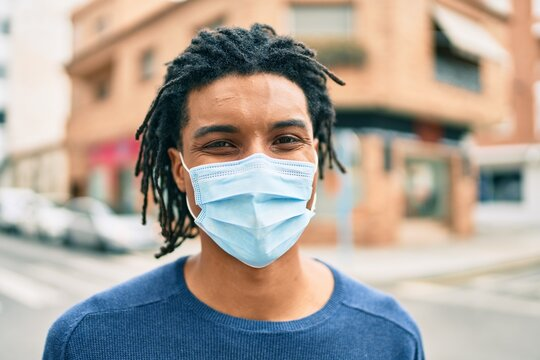 Young african american man wearing medical mask looking to the camera at street of city.