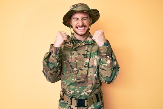 Young caucasian man wearing camouflage army uniform excited for success with arms raised and eyes closed celebrating victory smiling. winner concept.