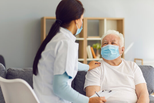 Caring supportive doctor visiting senior male patient at home during coronavirus pandemic