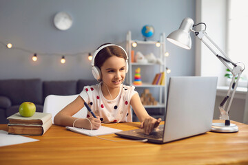 Home online schooling. Hardworking little girl in headset watching online lesson on laptop