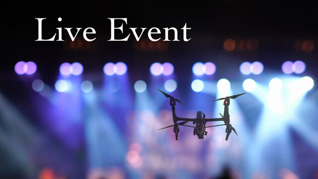 Closeup silhouette of Drone flying for taking video of Concert crowd and Abstract blurred photo of spotlight in conference hall, musical and concert concept