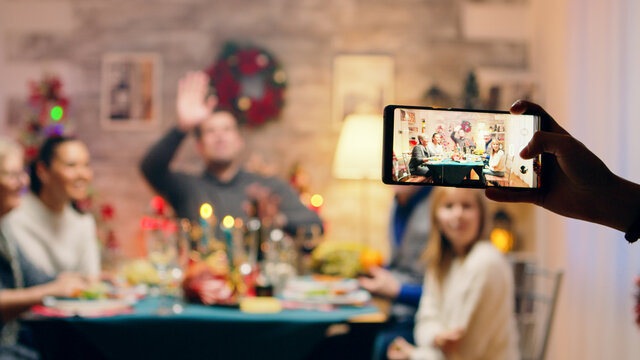 Girl taking photos of her family using smartphone at christmas reunion. Traditional festive christmas dinner in multigenerational family. Enjoying xmas meal feast in decorated room. Big family reunion