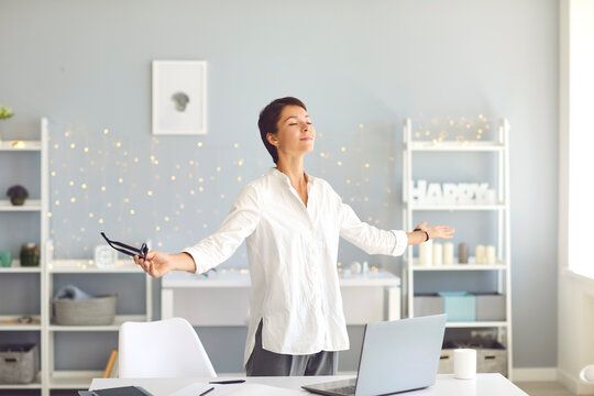 Happy relaxed business woman doing breathing exercises during break in her home office