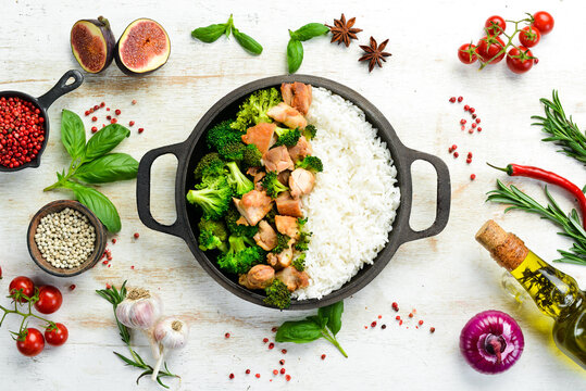 Boiled rice with broccoli and chicken fillet. In a frying pan. Healthy food. Top view.