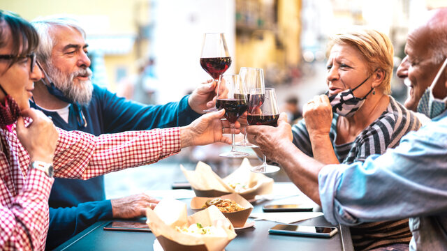 Senior couples toasting red wine at restaurant bar with face masks - New normal lifestyle concept with happy people having fun together at bar outdoors - Bright filter with focus on central glasses