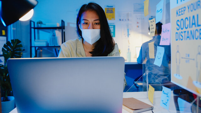 Happy Asia businesswoman wearing medical face mask for social distancing in new normal situation for virus prevention while using laptop back at work in office night. Life and work after coronavirus.
