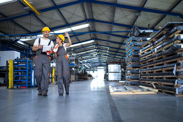 Fototapeta Factory workers in work wear and yellow helmets walking through industrial production hall and discussing about organization. obraz