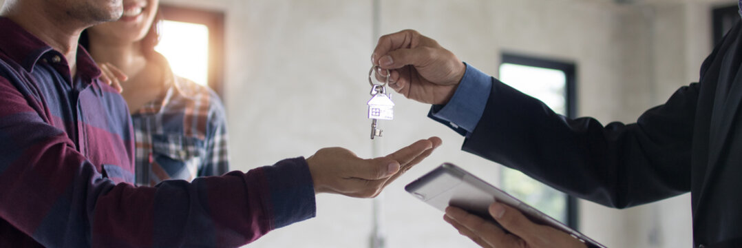 Bank agent give key of apartment or resident to young couple after successful discussing and finished contract, real estate concept