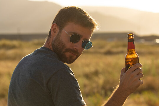 A young man, with glasses and a beard, drinks beer from a bottle, while enjoying the landscape and the sunset, in Galicia, northern Spain. Cheers!