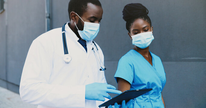 African American couple, man and woman, doctors colleagues in medical masks walking, talking and using tablet device. Male and female physicians tapping and scrolling on gadget computer. Communication