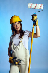 Pregnant woman wearing builder overall and protective helmet holding painting roller