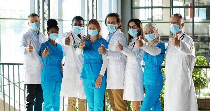 Mixed-races team of specialists, males and females doctors in hospital. International group of medics in medical masks. Protected workers giving thumbs up to camera. Multi ethnic physicians and nurses