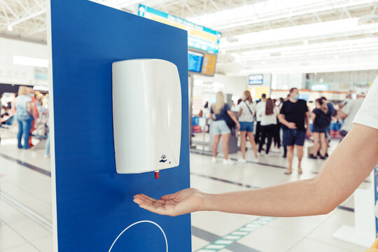 A female passenger disinfects her hands with an automatic sanitizer dispenser in the airport. Health care and protection from infection during the coronavirus pandemic