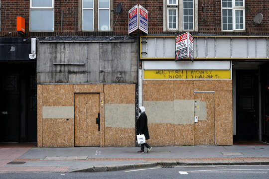 Pedestrian walks past bordered up retail stores in Croydon, south London