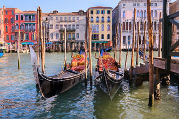 Gondolas moored by the pier on Grand Canal in Venice, Italy.