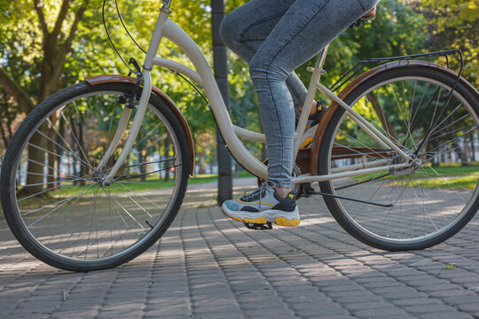A girl in jeans and sneakers rides a beige bike in the park among green trees and lawn