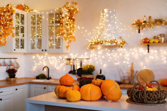 Autumn kitchen interior. Red and yellow leaves and flowers in the vase and pumpkin on light background