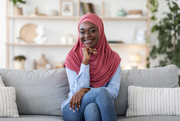 Door stickers Wall Decor With Your Own Photos Joyful young african muslim woman in hijab posing on couch at home