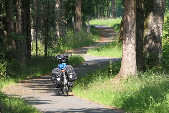 A touring bike is waiting for the driver. A fully packed touring bicycle stands in the sun on a path in the forest. The path meanders through the forest landscape.