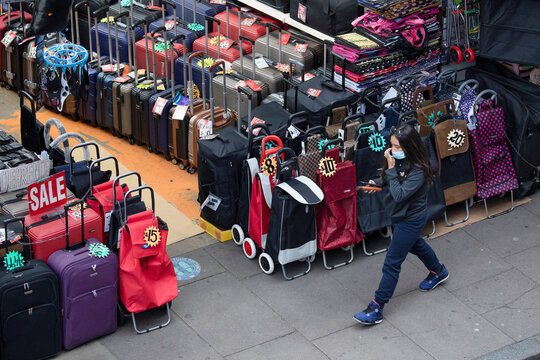 A pedestrian walks past goods for sale in Brixton, London, Britain