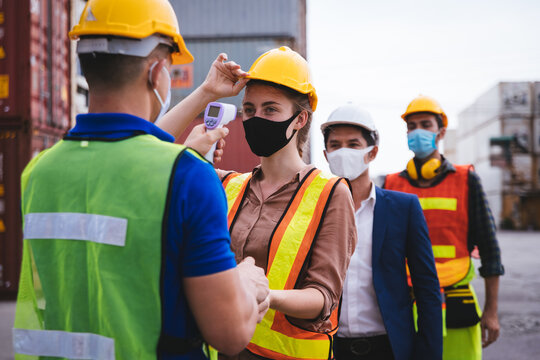 Worker scanning fever temperature with digital thermometer to construction site staff wearing hygiene face mask protect from Coronavirus or COVID-19. New Normal working life adaptation in 2020