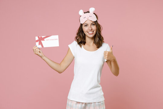 Smiling young woman 20s in pajamas home wear sleep mask showing thumb up holding gift certificate while resting at home isolated on pink background studio portrait. Relax good mood lifestyle concept.
