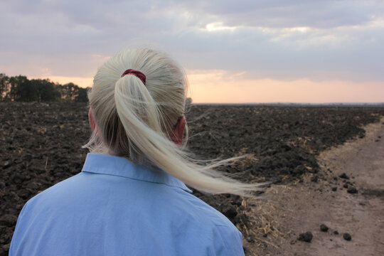 Back view of senior blonde woman standing in the field and looking at sunset. Stormy windy weather. Fall season