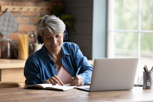 Modern elderly grey-haired 60s woman in headphones take online course or training on computer at home. Smart mature Caucasian female in earphones watch webinar make note study distant on laptop.