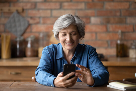 Smiling modern elderly 60s woman sit at table at home kitchen text or message on smartphone gadget. Happy smart mature grey-haired grandmother look at cellphone screen, browse internet on device.