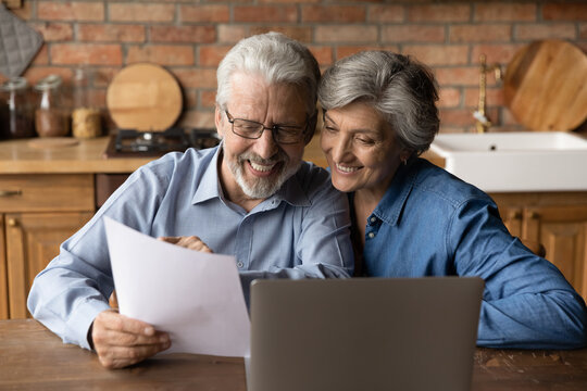 Happy elderly couple read postal paper document satisfied with banking health insurance contract or notice. Smiling mature man and woman consider good news in post paperwork letter correspondence.