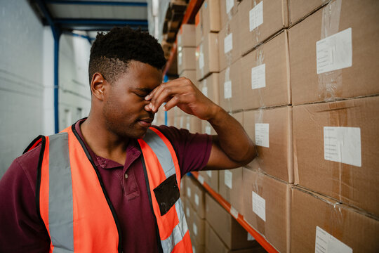 Male worker stressing after being threatened with retrenchment leaning against cardboard packages in warehouse