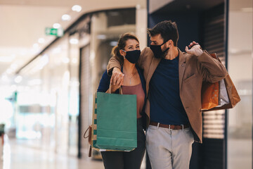 The young couple carries shopping bags and walks through the mall, wearing protective masks, life...
