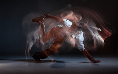 Guy breakdancer dancing hip-hop on the floor in studio on black background. Dance school poster. Long exposure shot