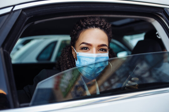Young business woman passenger wearing a medical mask looks out of a taxi car window. Business trips during pandemic, new normal and coronavirus travel safety concept.